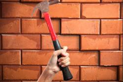 Чтобы быстрее и проще разобрать кирпичную стену, отбойный молоток надо направлять на места соединения кирпичей.