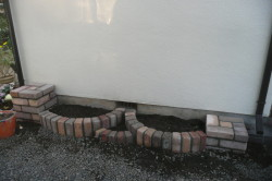 Полукруглая клумба с колоннами из кирпича