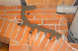 Трещину в кирпичной стене можно исправить с помощью нового раствора цемента.