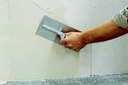 При реставрации стены трещины в кирпиче заполняются окрашенной мастикой с использованием шпателя.