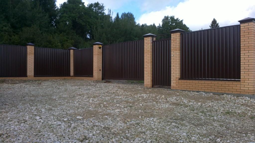 Заборы из профнастила, укрепленные столбиками из металлических труб или кирпича.