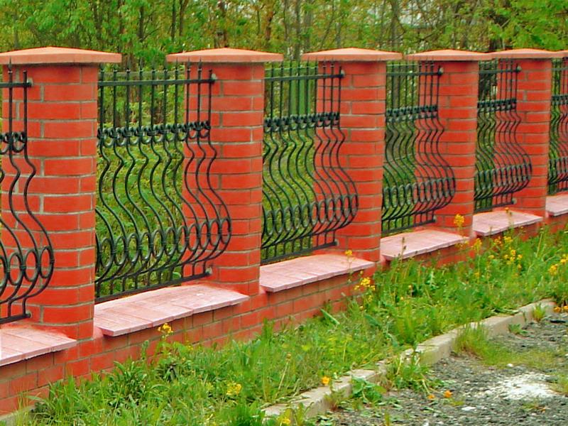 Заборы с кирпичными колоннами пользуются большой популярностью при ограждениях участков.